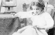 A monochrome archive photograph shows Helen Keller, around the age of eight, seated in a high barked armchair, next to a cloth-covered table, her legs resting upon a footstool. Clothed in a knee-length white dress and ankle boots, she reads with her left hand and points with her right hand out of shot.