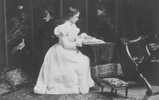 A monochrome archive studio image shows a young Helen seated at a fabric-draped table, dressed in a long, white, ornate Edwardian dress, her hands resting on a book of Braille. Behind her are screens decorated with with birds and the room is furnished with lavish fabrics and a Persian rug.