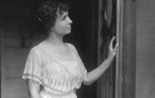 A monochrome archive photograph shows Helen, in her 20s, standing in an ornately carved doorway wearing a lavish floor-length frock dressed in layers of white lace. Her her left hand rest lightly on the door and she faces towards the right of the frame, her face pensive.