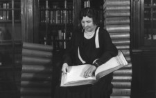 A monochrome archive photograph shows Helen dressed smartly in a black dress with pearls around her neck, sitting in a library, where print books behind glass fill oak shelves. On her lap rests a large Braille book. Next to her, stacks of Braille books tower twenty-high.