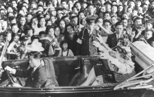 Helen and Annie sit in an open top car. In the background a deep crowd of people can be seen smiling and jostling to get a look at her. Helen has her arms outstretched, waving at the crowd.