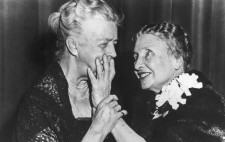 A monochrome archive image. The two women lean, smiling, towards each other. Helen reaches out her left hand to touch Eleanor Roosevelt's face while Roosevelt lightly guides Helen's arm.