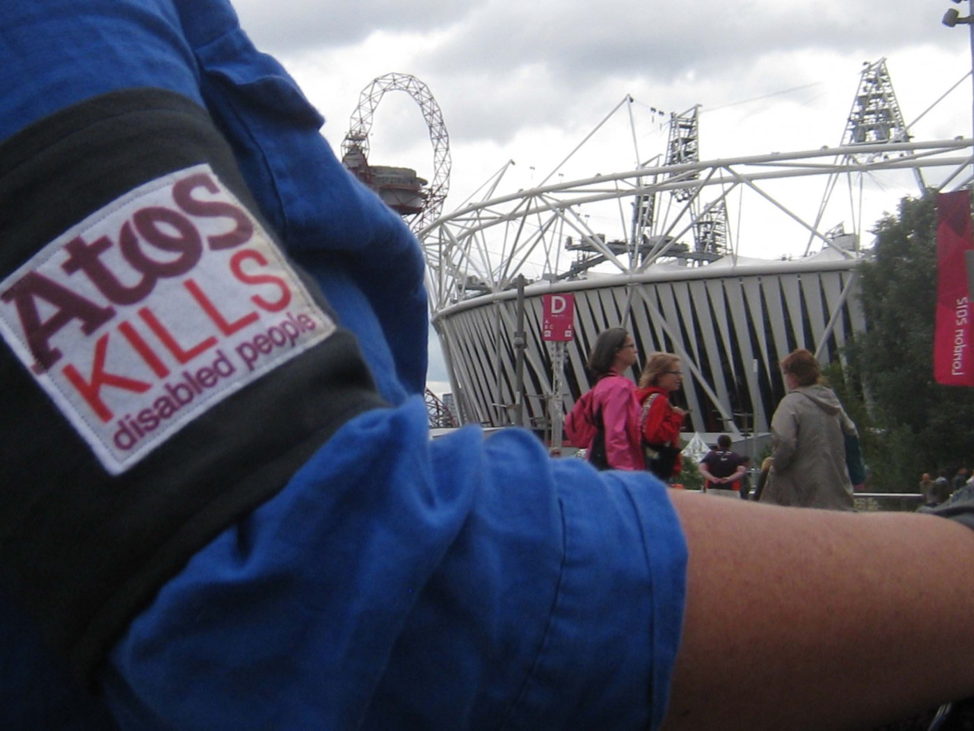 Worn over Liz Crow's blue shirt is a close-up of the Atos protest armband, showing parts of the slogan 'Atos kills disabled people' in purple and red on white. In the background is the Olympic stadium and a banner saying 'London 2012'.