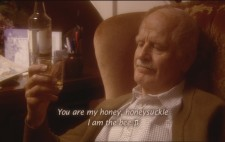 Old Walter sits in a comfortable chair gazing at his glass of whisky. Along the base of the screen, superimposed onto the picture, is the caption 'You are my honey, honeysuckle, I am the bee', followed by a music note symbol.