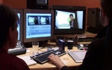 Liz sits in a post-production suite with an editor. In front of them are two monitors. One has a full-sized image from the film, with captions applied. The second shows two smaller versions of the same image, with an editing timeline below.