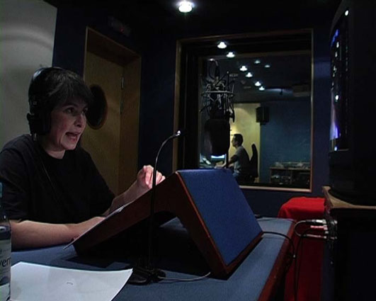 Director Liz Crow sits in a small studio recording audio description. She wears earphones and speaks into a microphone. On a small stand in front of her is a script and she is looking up to a monitor which plays the film. Beyond the studio window a sound editor sits at a mix desk.