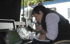 Under a black awning, Director Liz Crow sits on her wheelchair, looking intently at a monitor and holding a walkie-talkie ready to speak. Behind her in bright sunshine is the camera crew.