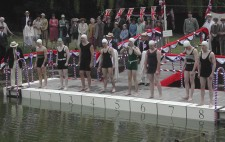 Eight swimmers line up along a pontoon festooned with patriotic red, white and blue, preparing to dive into lake water. The marshall, in navy blazer and straw boater, stands to one side. Behind the swimmers, supporters crowd the grassy banks.