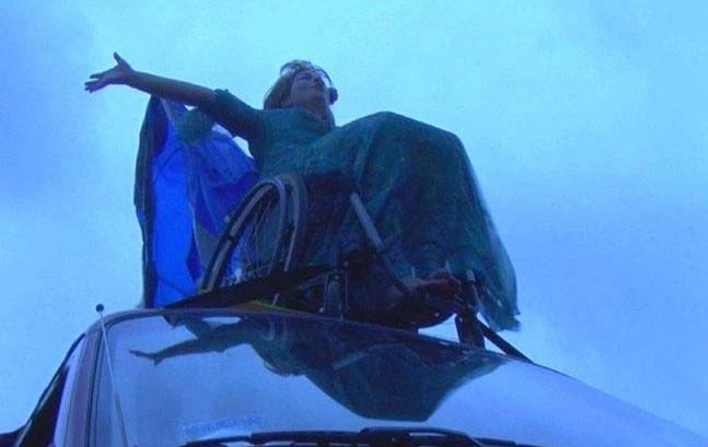 Against a half-light blue sky, a woman sits on her wheelchair, high up on top of a van roof. In a long dress, her arms thrown wide, blue fabric draped behind her, she tips back her head and whoops her joy.