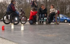 A group of five people from the production team gather around a weathered bronze memorial plaque set into pavement. Behind them are parked cars and the parkland trees of Tiergartenstrasse. Three votive candles have been set on the memorial.