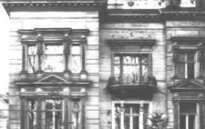An archive photograph showing the outside of an elegant villa, large windows, a balcony and a sweeping staircase to the raised front door.