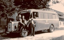 An archive photograph shows an old-fashioned bus, its windows blacked out, a Nazi eagle on the side. Three men pose for the photograph: one sits on the high wheel arch, another leans against it, a third leans out from the front passenger window.