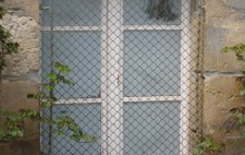 A close up of the outside of one of a lower ground floor window, whited out and with a metal grill over it. On the ground are scatted wood chippings and leaves from nearby planting frame the window.
