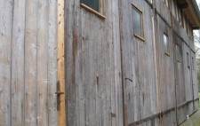 The outside of the garage, built from planks of wood, with three sets of double doors doors, each with high window panels.