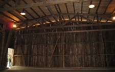 A photograph shows a cavernous barn-like wooden structure dwarfs a door open to the outside where people peer in.