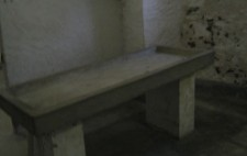 A small room with rough limewashed stone walls and rough stone floor, a small window up high. In the centre is a grey stone table with raised sides, a drainage pipe at one end which runs to the floor.