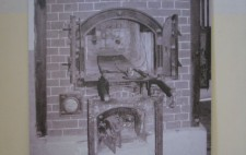Photograph showing a large photographic reproduction placed against a wall showing an old-fashioned brick bread oven, it doors open.