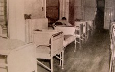 An archive photograph shows an old-fashioned hospital ward tightly packed with rows of empty metal-framed beds. A member of staff makes up one of the beds.