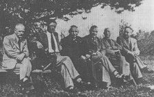 An archive photograph shows six men, ranging in age from thirties to fifties, wearing suits and ties, sitting in a row on benches under a tree in a park. Turned to the camera, their faces are neutral.