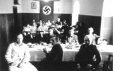 An archive photograph showing a wood panelled dining room, long tables covered in white cloths. Around twenty staff members sit, turned to the camera, wearing a mixture of white coats, civilian clothes and uniforms.