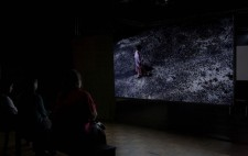 An audience watches the drama on the large screen suspended in pitch dark space. Filmed from above, a woman, dressed in a shabby pink dress and cardigan, sweeps a dark path across a large swathe of gravel.