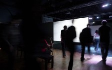 In a dark gallery space, the film on the first screen has ended and the screen shows bright white. Audience members move around the side of the screen into the space behind.