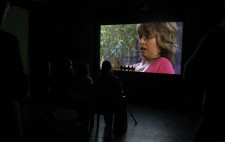 An audience sits in front of the second screen, watching Sophie projected in close-up, shown in a domestic setting, greenery visible in the window behind her.