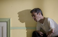 Mat Fraser crouches to the right of the frame, his shadow reflected large on the wall behind him.