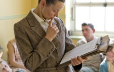 An office, dressed in a 1930s grey tweed suit, stands in the middle of the ward examining a typed list on her  clipboard. Behind her, inmates sit or lie on dormitory beds.