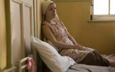 An inmate sits on a bed and rests up against the wall behind her, a window to her right. She wears white headscarf and floral dress and gazes far distance.