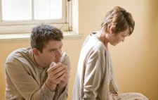 Two of the inmate extras sit on a bed between takes, both gazing far distance. One, a man dressed in a grey shirt and ripped green trousers, sits facing the camera. The other, a woman dressed in a grey cardigan and a checkered skirt, sits with her back to him.
