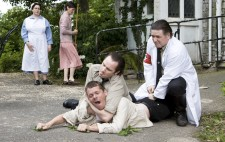 Inmate Otto is sprawled on the ground outside the institution, an orderly pinning him down in a necklock. A second orderly in white coat and red Nazi armband kneels down. In the background the nurse and Elise watch helplessly.