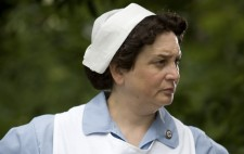 The Nurse stands with her hands on her hips, dressed in a pale blue nurse's outfit and white apron, a small Nazi swastika badge on her lapel.