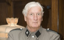 A man in a grey military style outfit and wearing a Nazi swastika armband stands, arms crossed, looking at the camera.