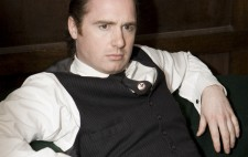 Actor Canice Bannon, who plays the Orderly, between takes. He sits in an armchair holding a sherry glass. He has slicked back hair, and wears a white shirt, a black waistcoat and tie emblazoned with a swastika.