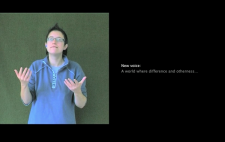 A woman faces camera, communicating in sign language and filmed against greenscreen. To her left is captions text, white on black, reading 'New voice: A world where difference and otherness...'