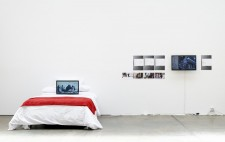 In a white-walled gallery, is a double bed with a white quilt and a throw of red fabric. Leaning against the pillows is a video display screening Reflections from the Bed. On the wall behind are images from...