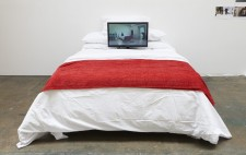 In a white-walled gallery, is a double bed with a white quilt and a throw of red fabric. Leaning against the pillows is a video display screening Reflections from the Bed.