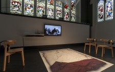 A large mat displaying a life-sized photograph of Liz's empty double bed, white bedding and a red fabric throw, lies flat on the black floor of the stage. Grouped around it are four chairs, each with a headset looped over its back. At the pillow end of the   mat, mounted on the wall, is a screen showing the film Reflections from the Bed. Above the stage stretch the stained glass windows of this former church.