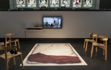 A large mat displaying a life-sized photograph of Liz's empty double bed, white bedding and a red fabric throw, lies flat on the black floor of the stage. Grouped around it are four chairs, each with a headset looped over its back. At the pillow end of the   mat, mounted on the wall, is a screen showing the film Reflections from the Bed.
