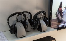 Three cordless headsets on a white shelf, next to a TV showing the film Reflections from the Bed.