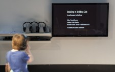 A child looks up at a wall-mounted TV monitor which displays the credits for the film.To the left is a row of three cordless headsets.