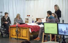 Liz Crow lies on the stage in her bed, with four people seated around it, holding microphones. A sign language interpreter stands to the side of the bed. Stage right are two monitors.