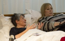 A close up of Liz Crow and Dawn Willis, reclined next to each other on the bed. Liz looks over to Dawn and gesticulates, as Dawn types.