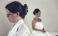 In the foreground Laura stands facing left of frame in a white coat. In the background, against a white backdrop, Isolte, wrapped in a white sheet, faces away from her.