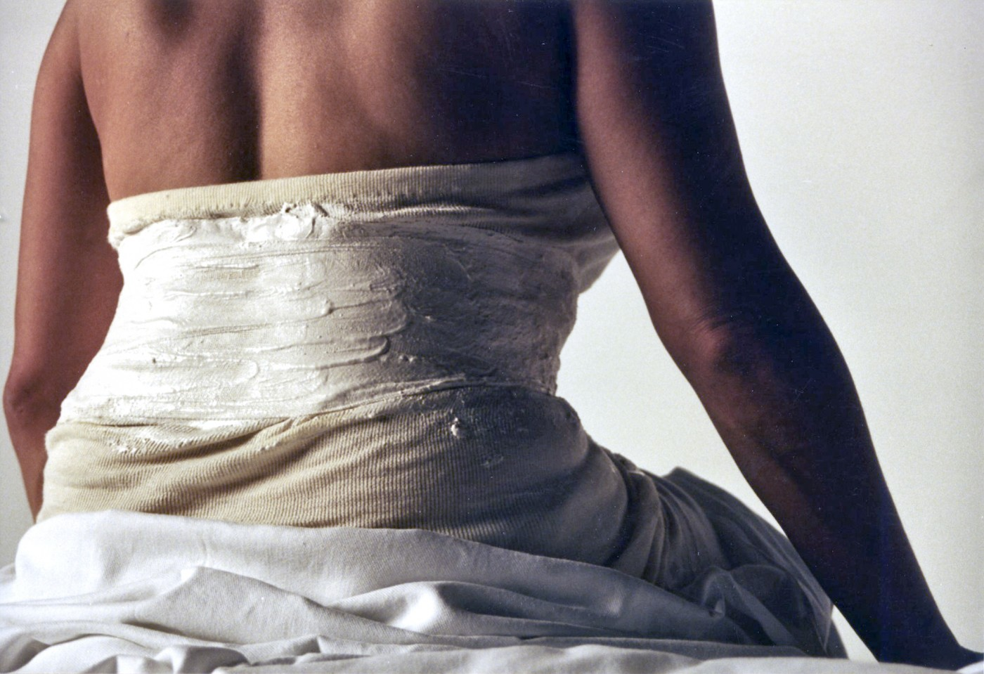 In close up, Isolte sits on a medical counch, her back to camera, her lower half draped in a white sheet and the unpainted corset constructed around her.