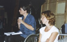 Director Liz crow sits on her wheelchair, next to another member of the crew, a script on her lap and a styrofoam cup in her hands. They both gaze at events beyond the shot.