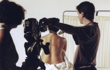 Carol adjusts her camera tripod, while a focus puller measures the distance from the camera to actor. Isolte sits facing a stark white backdrop, her back to camera and torso wrapped in a sheet, ready for the corset to be applied.