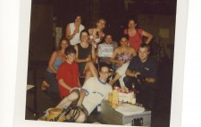 A polaroid of the 10 crew from the shoot, gathered in the film studio, surrounded by equipment. In front of them is a silver equipment carry case, on which beers and drinks are rested. They grin and pose for the camera.