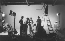 A monochrome photograph: a studio is filled with lights on stands, ladders and boxes of film kit. Against a white backdrop, Frida (Isolte Avila) faced forward, wrapped in the white plaster corset.  The camera is trained on Isolte, the crew in place. On a tall ladder, Mel holds a small pot extended on a pole high above Isolte's head.